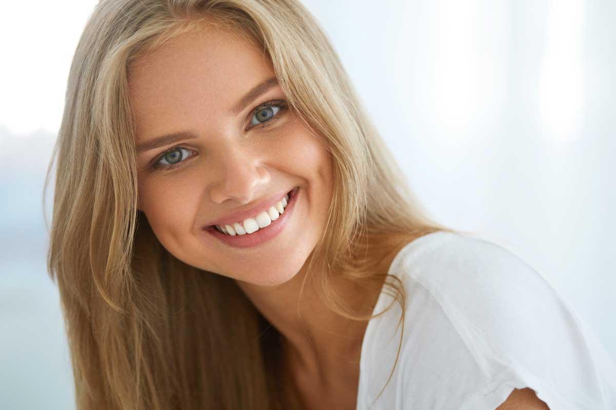estetica dei denti:ragazza bionda abbronzata sorridente