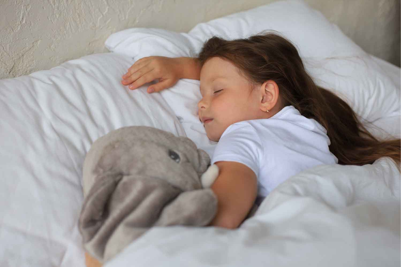 quando rimuovere il ciuccio ai bambini: bambina che dorme senza ciuccio con elefantino