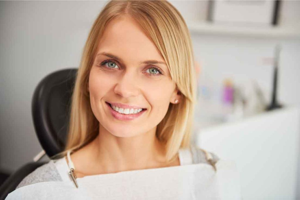 sbiancamento dentale: donna bionda sorride su poltrona dentista
