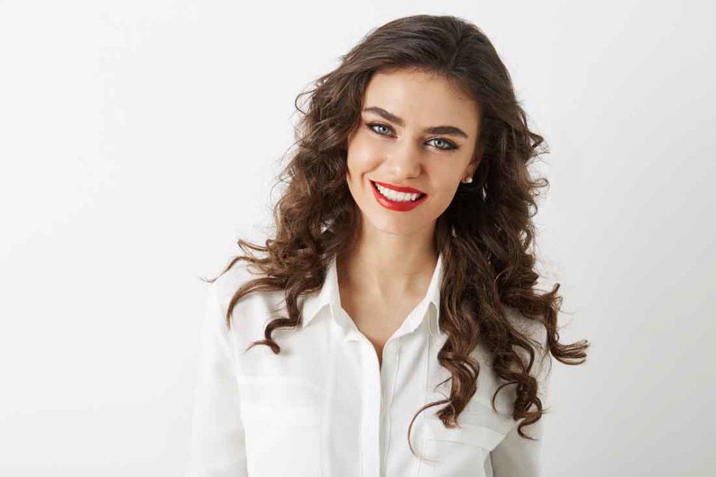 sbiancamento dentel: ragazza mora su sfondo bianco con rossetto rosso